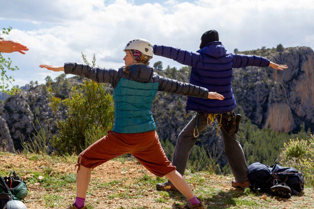 """Yoga-Haltung """"Krieger II"""" zur mentalen Vorbereitung aufs Klettern. Im Hintergrund schöne Sicht auf Felswand."""